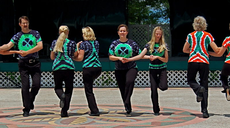 Picture, Men and women on stage, wearing tie-dyed shirts and Irish dancing in