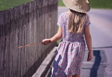 Girl touching wood fence with wood stick